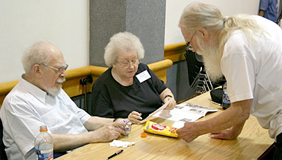 Guest of honor Phil Klass, from left, and his wife Fruma talk with Pulpcon's Rusty Hevelin at their table Friday afternoon.