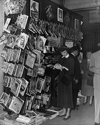 "Betsy Drake poses at a ""newsstand."""